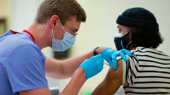 a person getting a vaccine shot from a md phd student